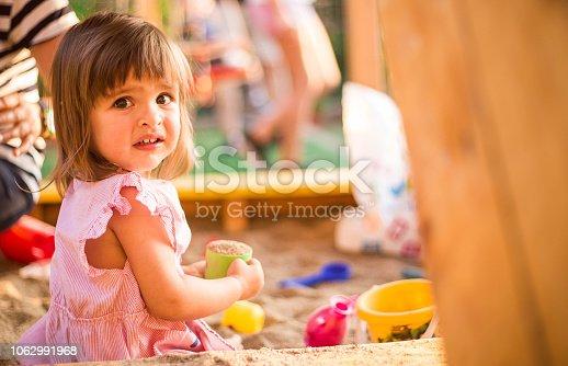 Cute little girl playing in sandbox