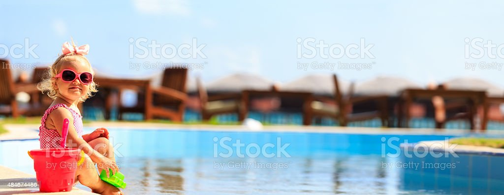 cute little girl playing in swimming pool at beach stock photo