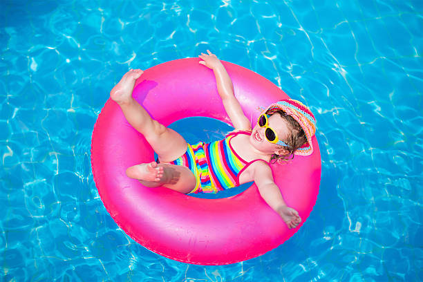 niedliche kleine mädchen spielen im swimmingpool - sonnenbrille kleinkind stock-fotos und bilder
