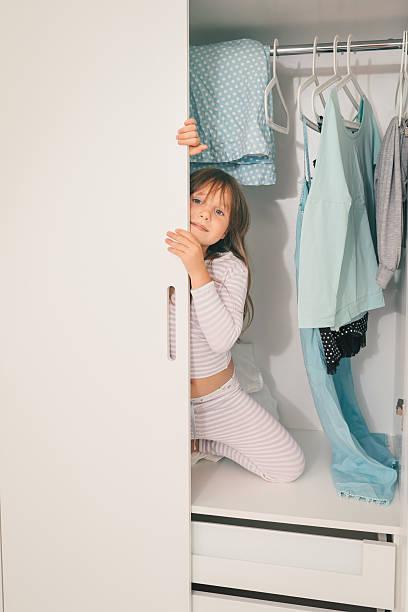 cute little girl playing in wardrobe - mutterkleiderschrank stock-fotos und bilder