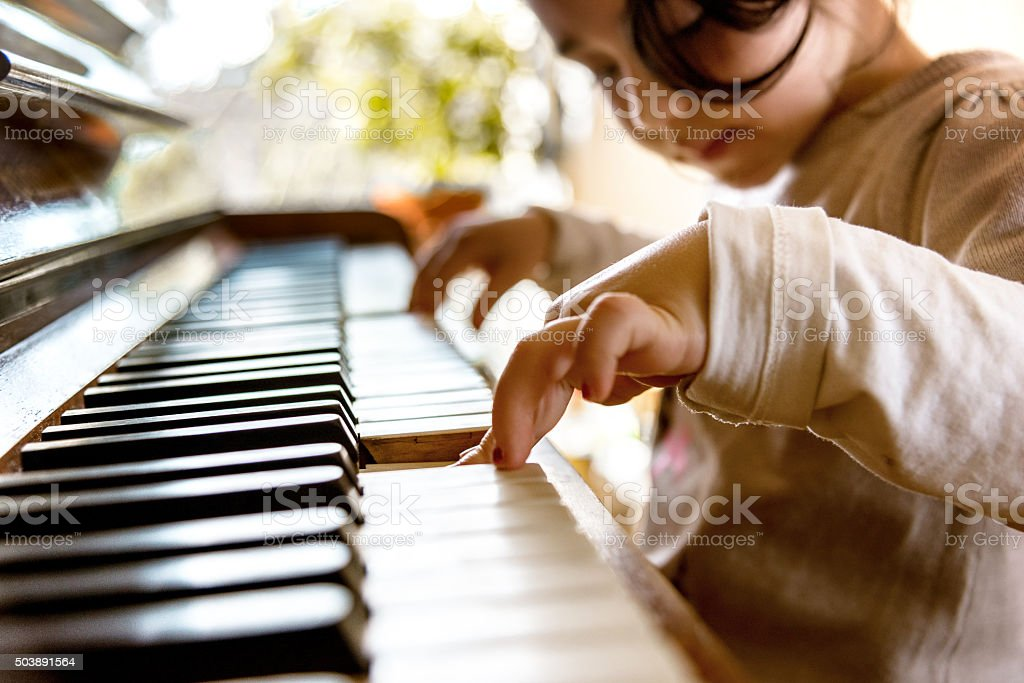 cute little girl playing on old piano stock photo