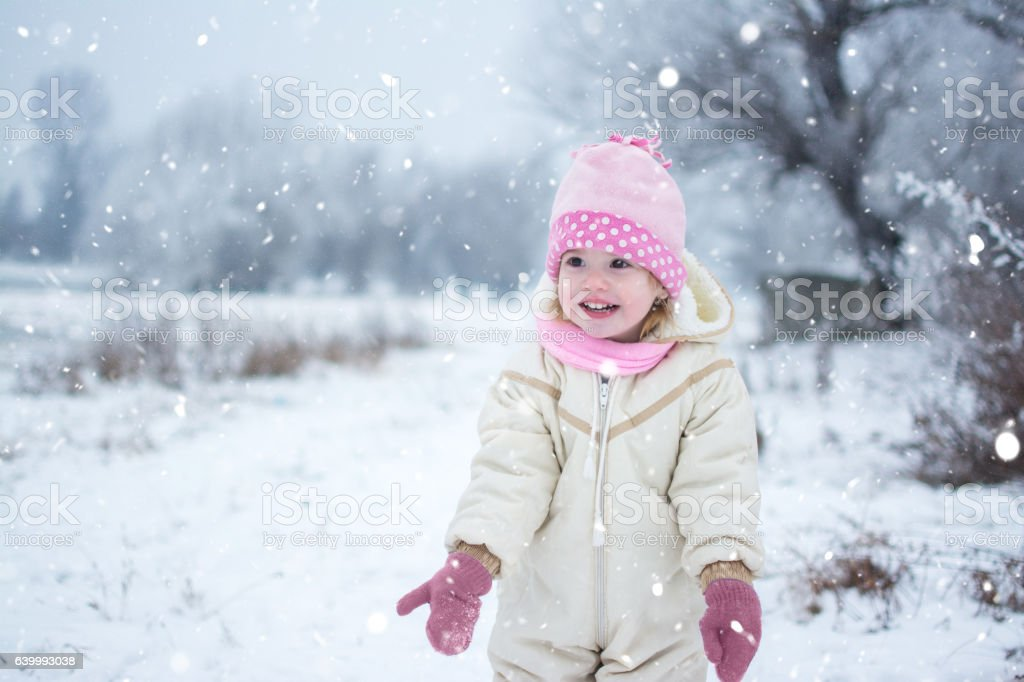 Cute little girl playing on snow in the park. stock photo