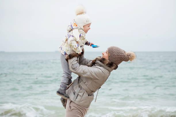 niedliche kleine mädchen spielen am sandstrand. - gute winterjacken stock-fotos und bilder