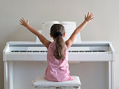 Cute little girl playing piano at home