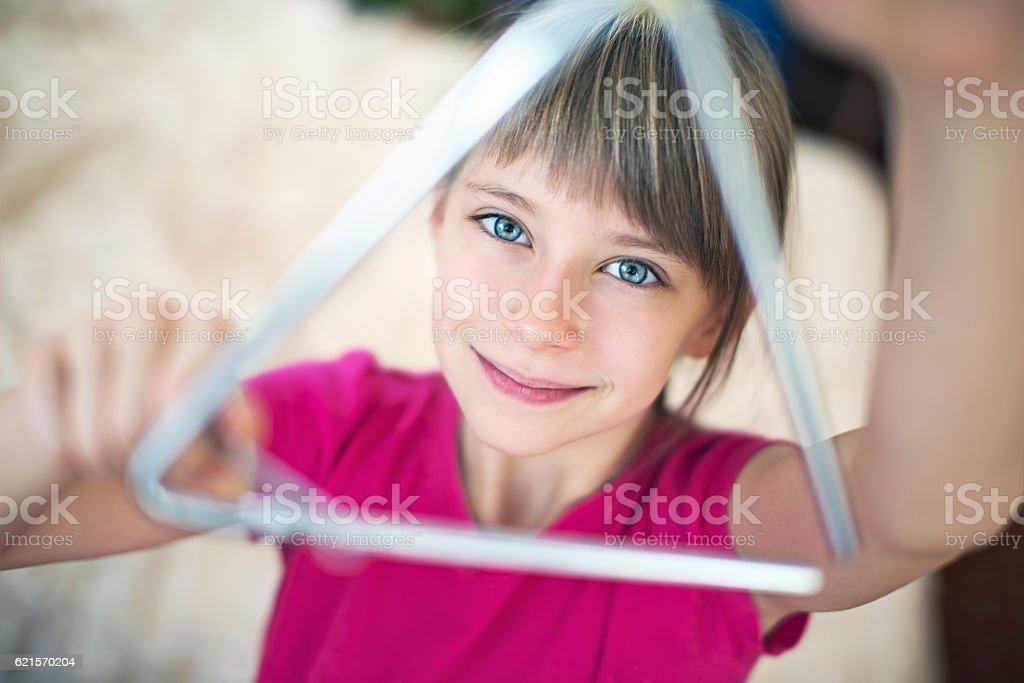 Cute little girl playing triangle photo libre de droits