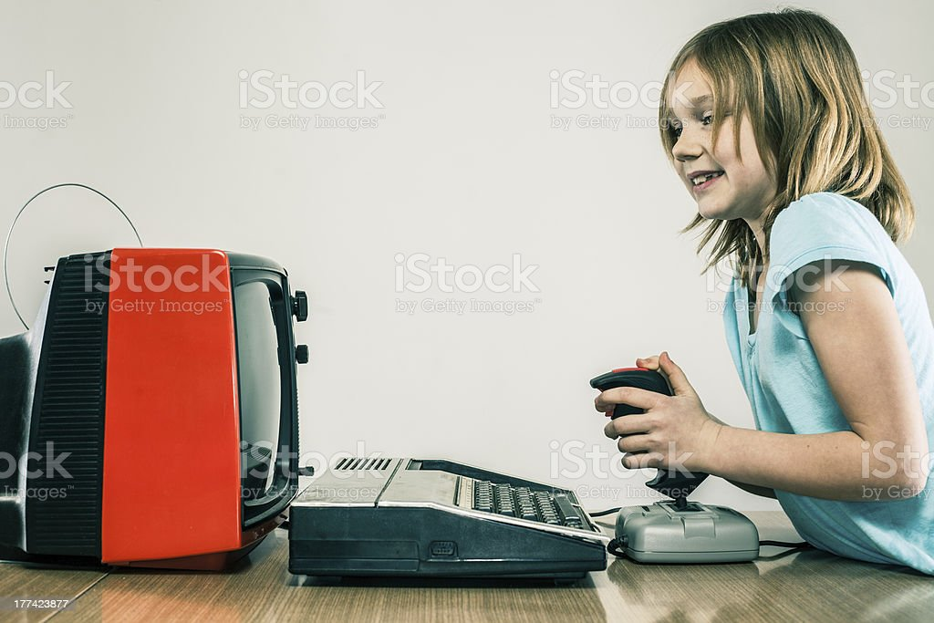 Cute little girl playing vintage video games with retro joystick stock photo