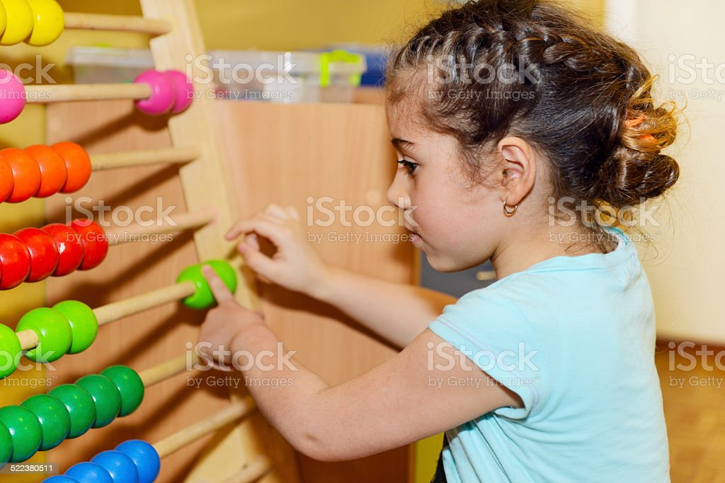 Cute little girl playing with abacus stock photo