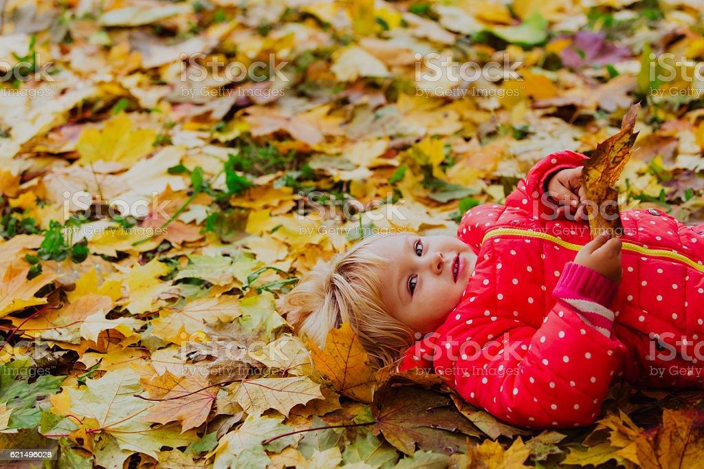 Mignonne Petite fille jouant avec des feuilles d'automne photo libre de droits
