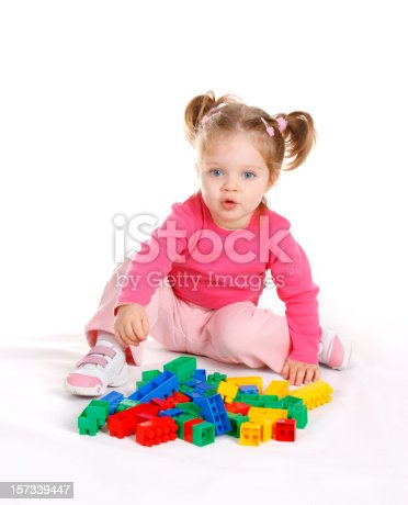 istock Cute little girl playing with blocks, on white background 157339447