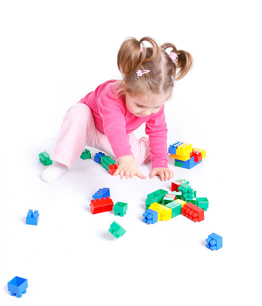 Cute little girl playing with blocks stock photo