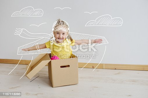 Cute little girl playing with cardboard airplane on a white background. A child dreams of flying. The kid imagines .