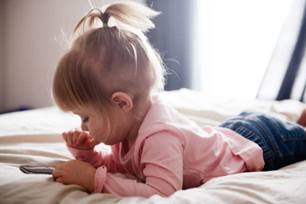 cute little girl playing with cell phone on a bed - manonallard stock photos and pictures