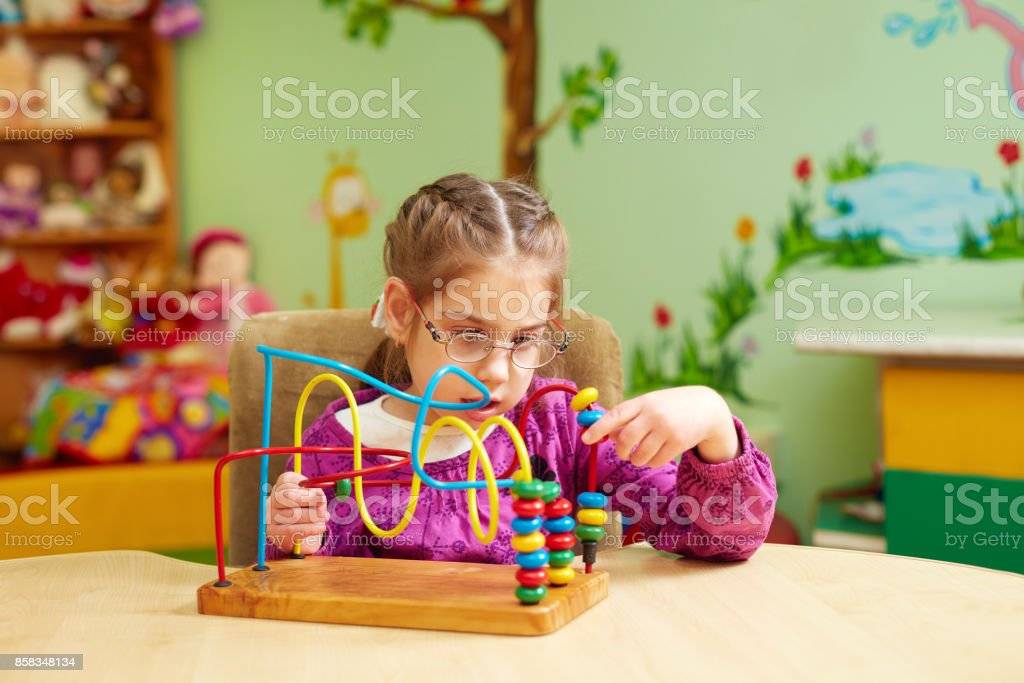 cute little girl playing with developing toy in kindergarten for kids with special needs - foto stock