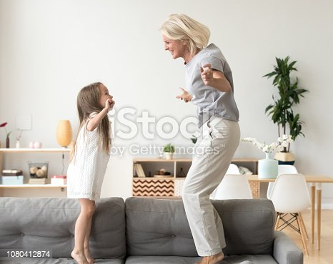 istock Cute little girl playing with grandmother jumping on couch together 1080412874
