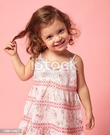 Cute little girl playing with her hair, smiling at camera in front of pink background.