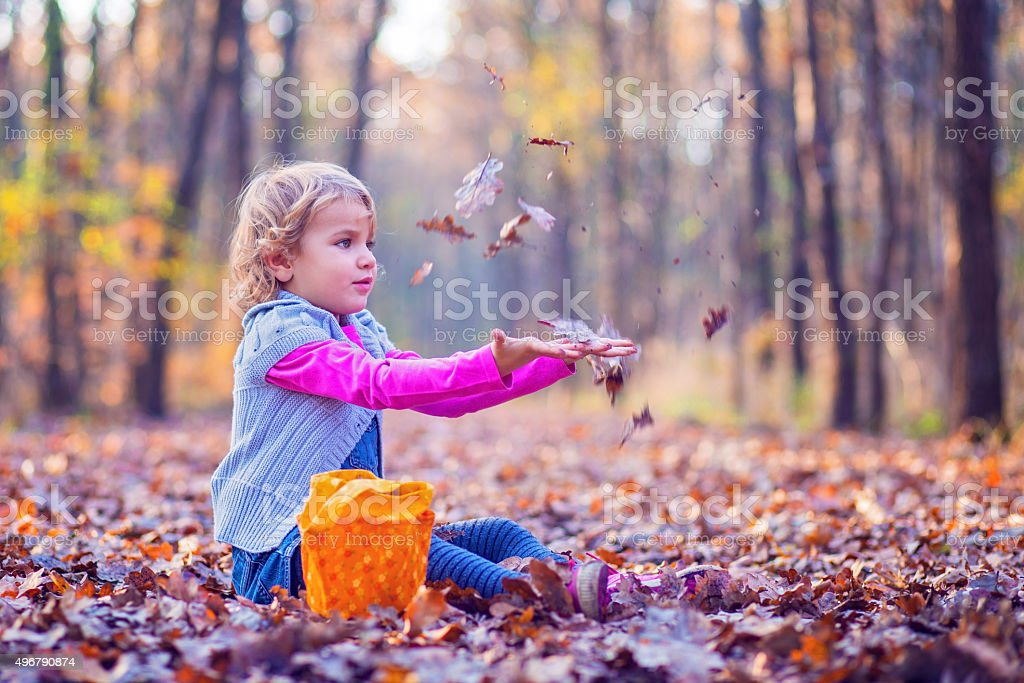 Cute little girl playing with leaves in the forest stock photo