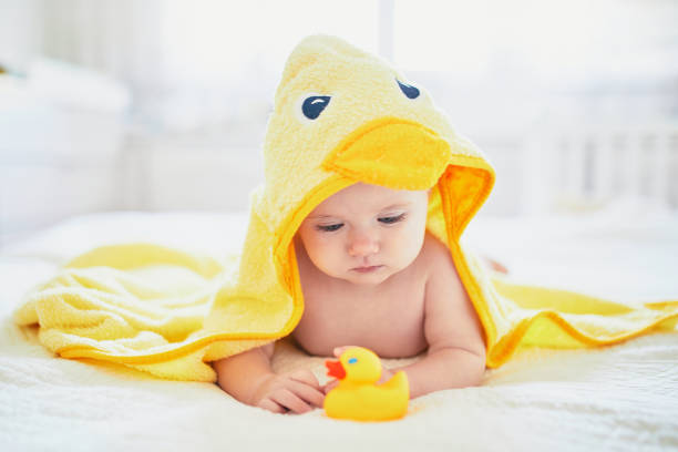 Cute little girl playing with rubber duck after having bath stock photo
