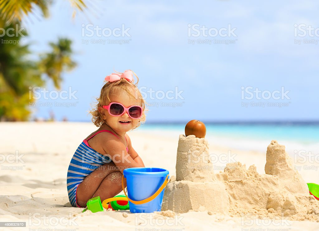 cute little girl playing with sand on beach​​​ foto
