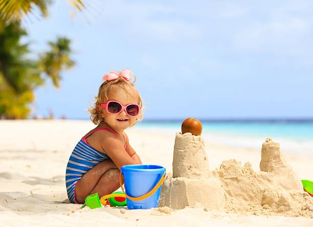 niedliche kleine mädchen spielen mit sand am strand - sonnenbrille kleinkind stock-fotos und bilder