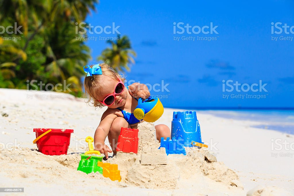 cute little girl playing with sand on beach
