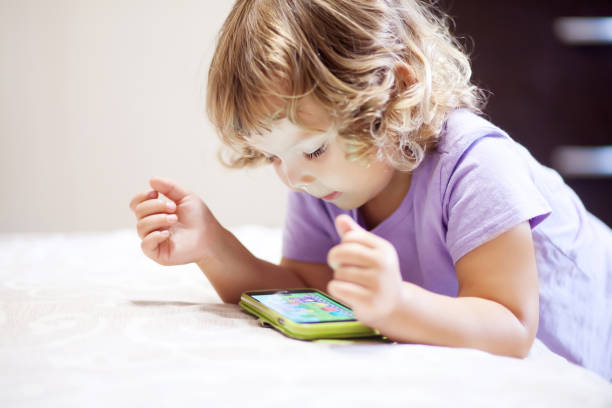 Cute little girl playing with smartphone. stock photo