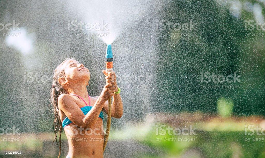 Niedliche kleine Mädchen gießt sich aus dem Schlauch, macht einen Regen. Heißen Sommer Tag Vergnügen – Foto
