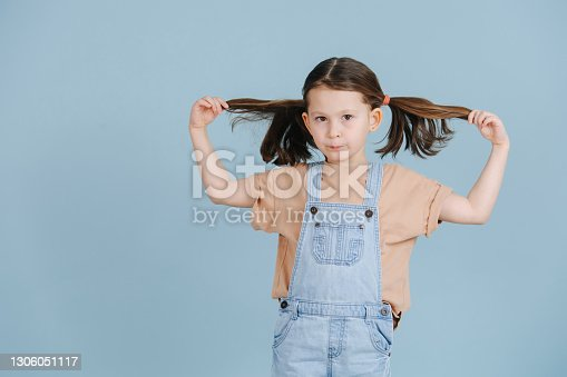 Cute little girl pulling her ponytails to sides, posing for a photo over blue background. She wears jeans overalls and brown shirt.