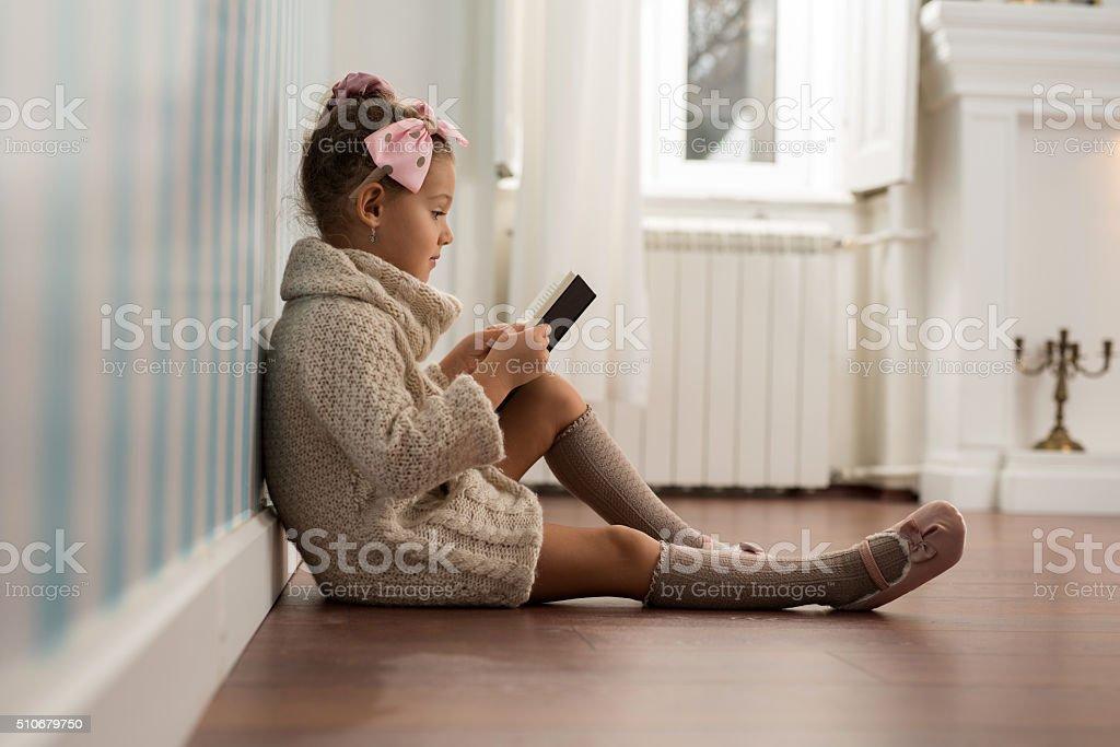 Cute little girl reading a book on floor. stock photo