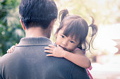 Father and child,cute little girl resting on her father's shoulder in the park, vintage filter effect