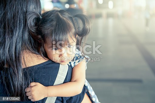 Mother and child,cute little girl resting on her mother's shoulder in the train station, vintage filter effect,selective focus