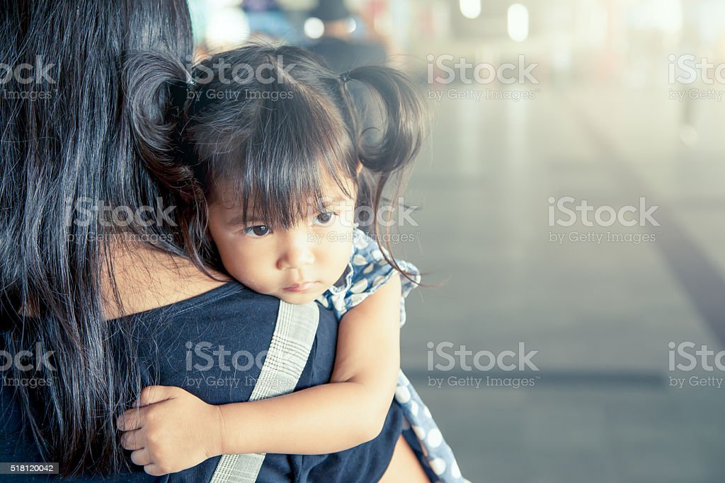 cute little girl resting on her mother's should stock photo
