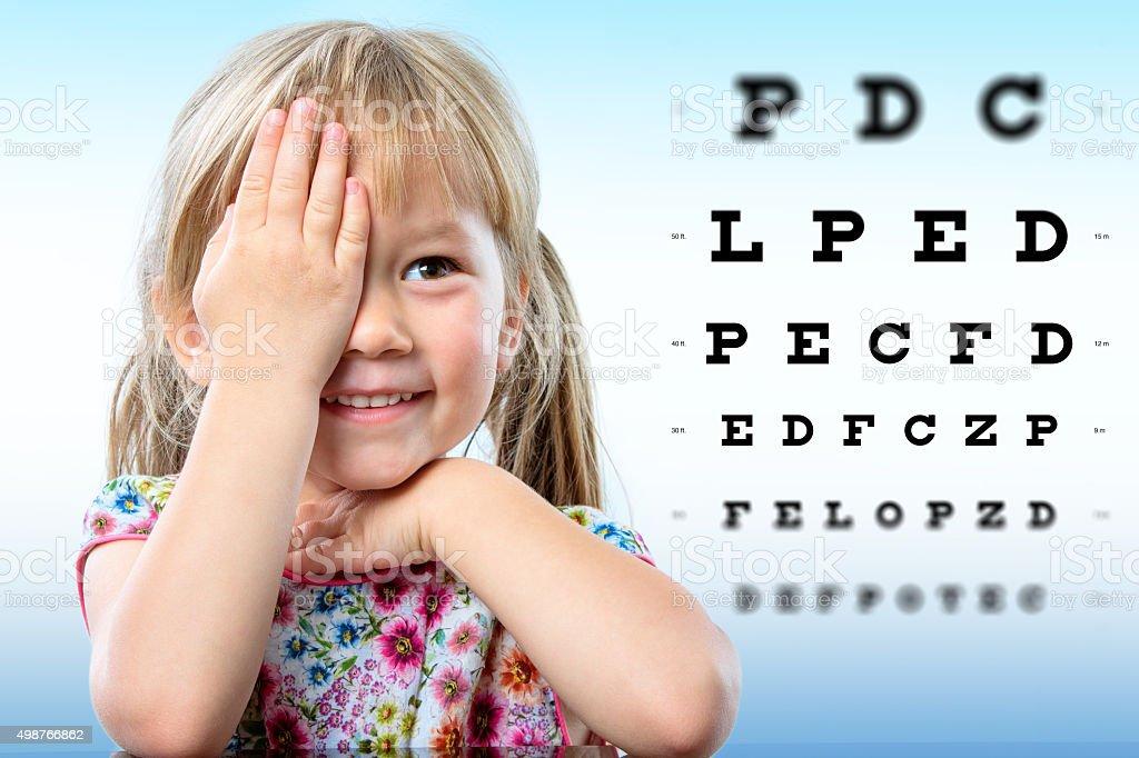 Niedliche kleine Mädchen, die Überprüfung des Augenlichts führen. – Foto