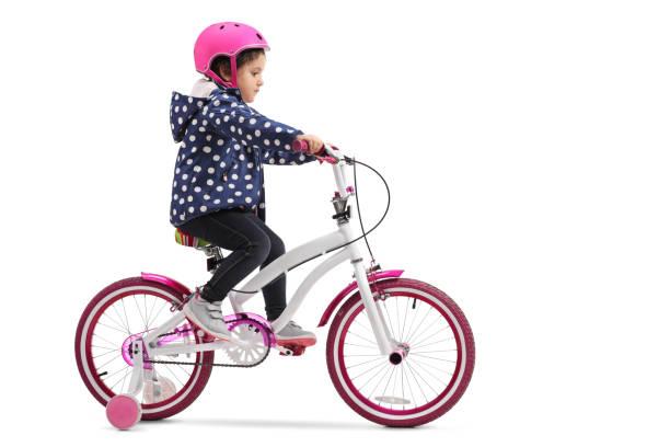 Cute little girl riding a bike stock photo
