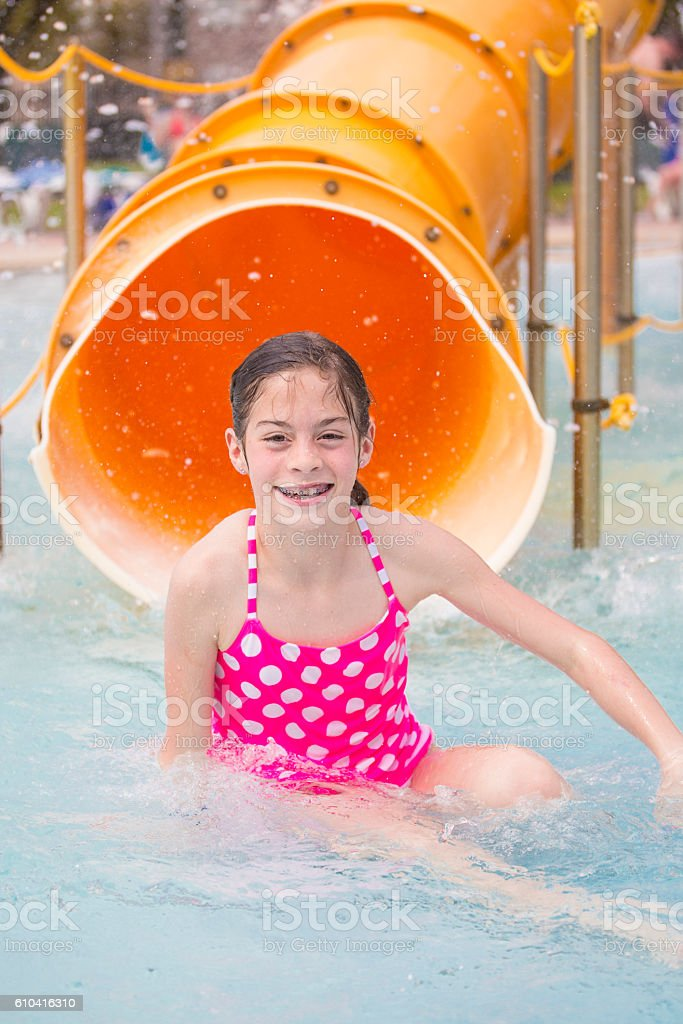 Cute little girl riding down a water slide at a water park stock photo