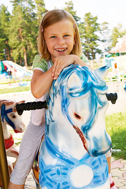 cute little girl riding on a carousel stock photo