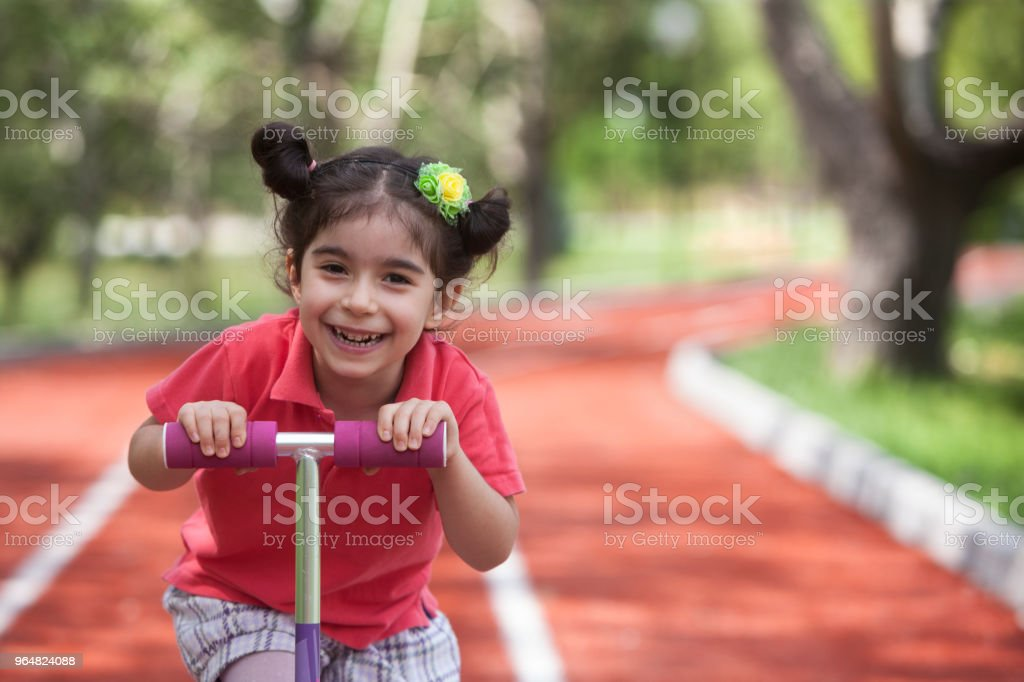 Cute little girl riding push scooter royalty-free stock photo