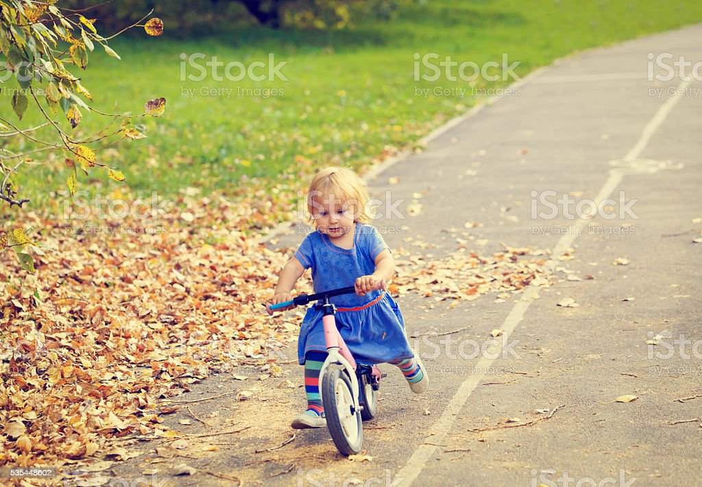 cute little girl riding runbike in autumn stock photo