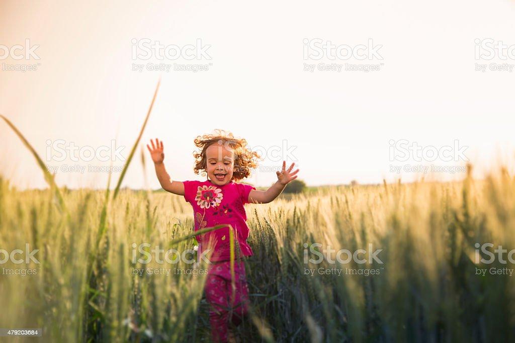 Cute little girl running through field stock photo
