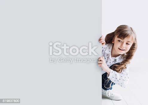 istock Cute little girl showing gray banner 519837800