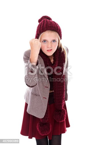 Portrait of cute little girl showing her fist in anger against white background