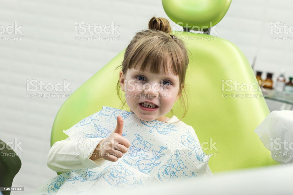 Cute little girl showing thumb up sign at dentist's office (clinic) stock photo