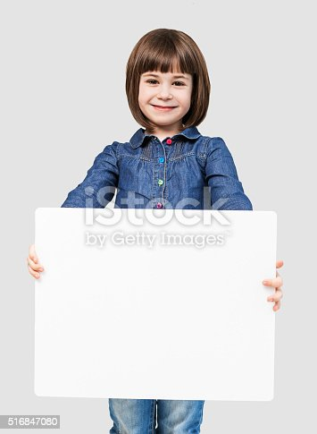 519837800 istock photo Cute little girl showing white banner 516847080