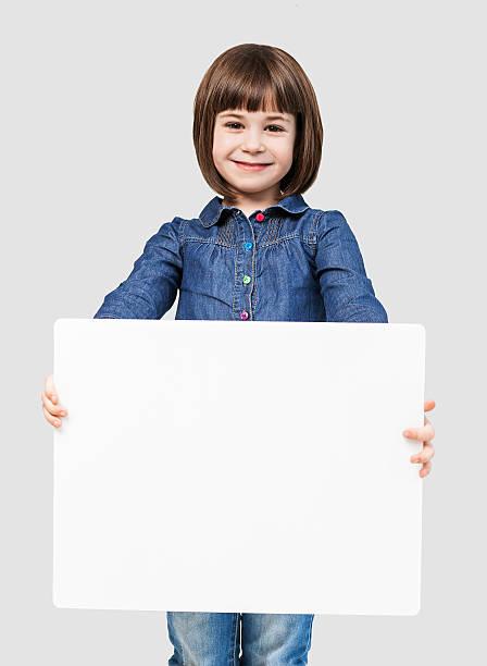niedlich kleines mädchen zeigen weißen banner - sprüche kinderlachen stock-fotos und bilder