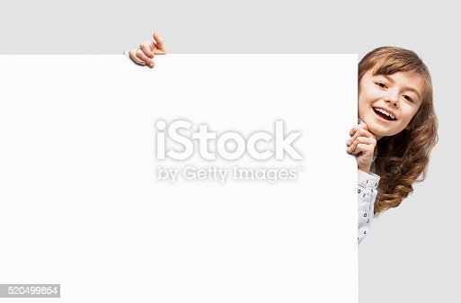 istock Cute little girl showing white banner 520499854