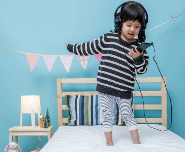 Cute little girl sing a song with smartphone in her bedroom, Happy asian child little girl listening the music with headphone on the bed, technology concept Cute little girl sing a song with smartphone in her bedroom, Happy asian child little girl listening the music with headphone on the bed, technology concept affective stock pictures, royalty-free photos & images
