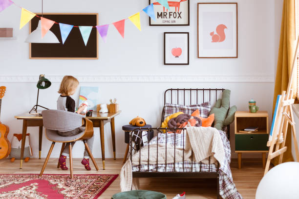 Cute little girl sitting at desk in her stylish vintage bedroom with workspace stock photo
