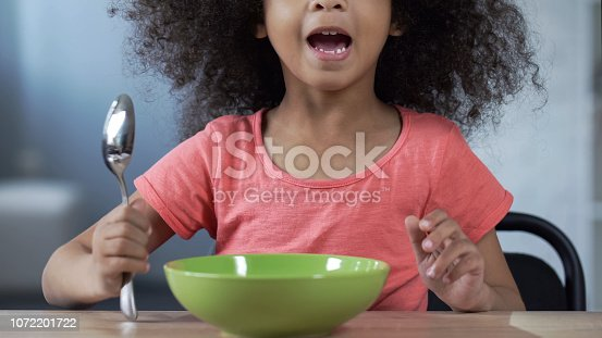 Cute little girl sitting at table with spoon and asking for dinner, hungry kid