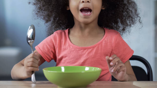 Cute little girl sitting at table with spoon and asking for dinner, hungry kid Cute little girl sitting at table with spoon and asking for dinner, hungry kid hungry child stock pictures, royalty-free photos & images