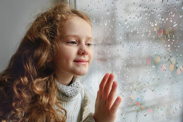 Cute little girl sitting by the window. – Foto