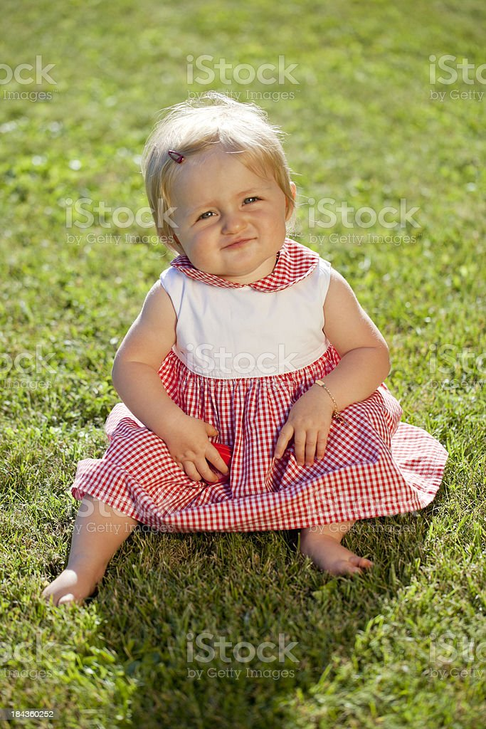 Cute little girl sitting in the garden royalty-free stock photo